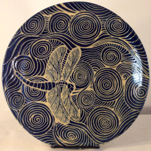 Round stoneware plate with sgraffito carved dragonfly and water motif