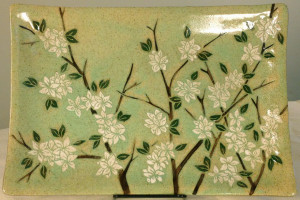 Stoneware platter with sgraffito carved blossoms motif